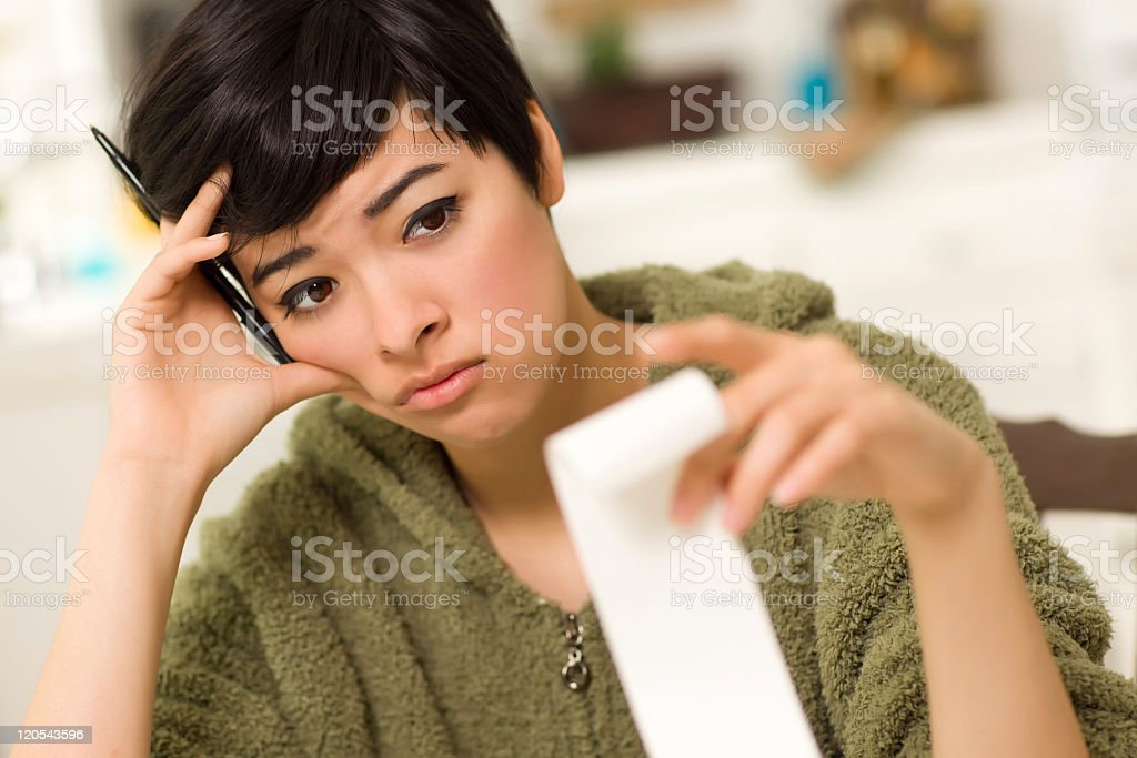 Young woman with distressed expression holding invoice stock photo