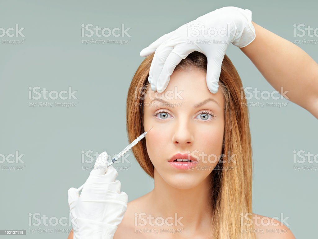 young woman with doctor hands injecting botox royalty-free stock photo