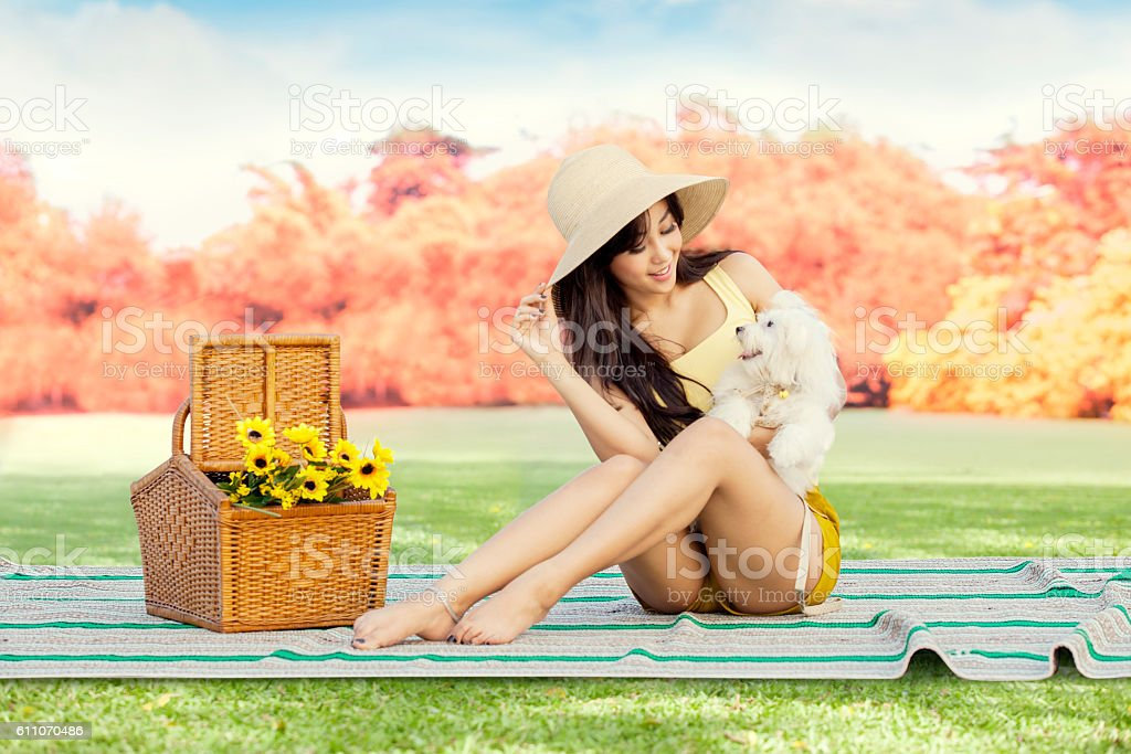Young woman with dog sitting at the park stock photo