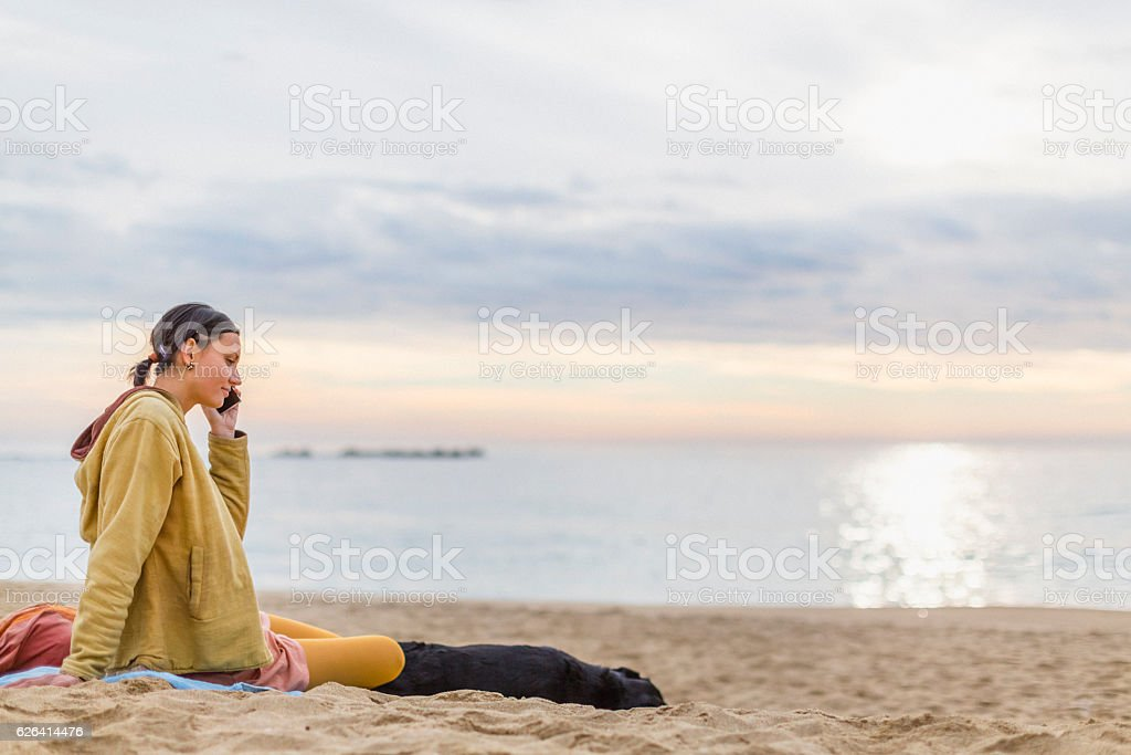 Young woman with dog talking on the phone stock photo