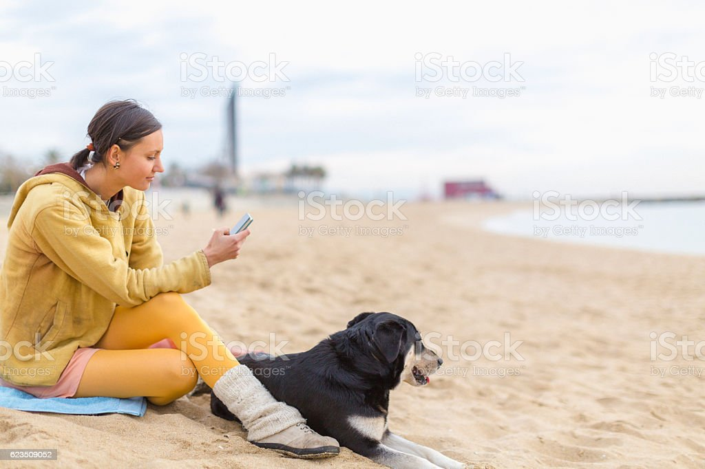 Young woman with dog texting with smart phone stock photo
