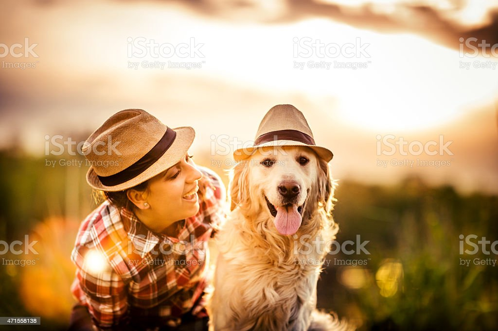 Young woman with dog wearing matching hats stock photo