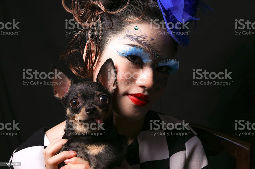 young woman with fantasy makeup and pet chihuahua stock photo