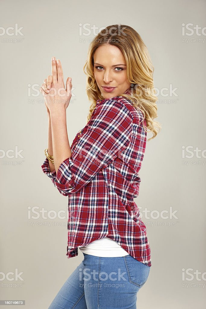Young woman with finger gun on grey background stock photo