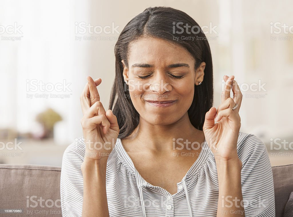 Young woman with fingers crossed at home stock photo