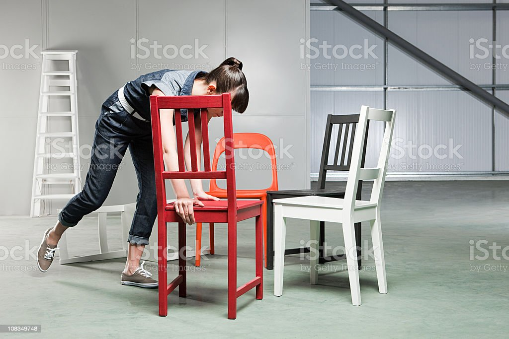 Young woman with five chairs royalty-free stock photo
