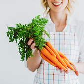 Young woman with fresh carrots