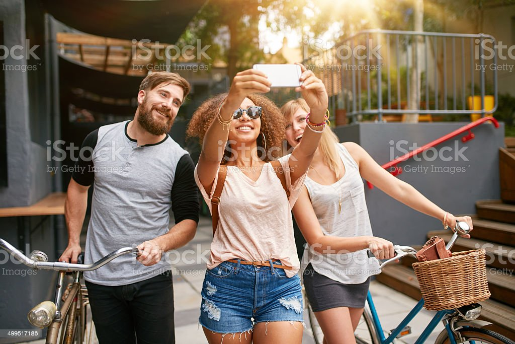 Young woman with friends taking selfie stock photo