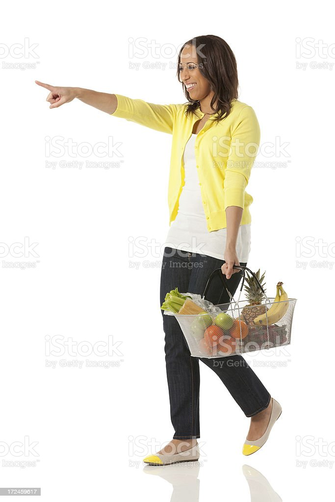 Young woman with fruit basket and pointing royalty-free stock photo