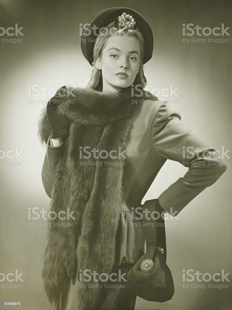 Young woman with fur collar posing in studio, (B&W), portrait royalty-free stock photo