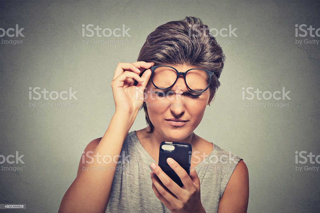 young woman with glasses having trouble seeing cell phone stock photo