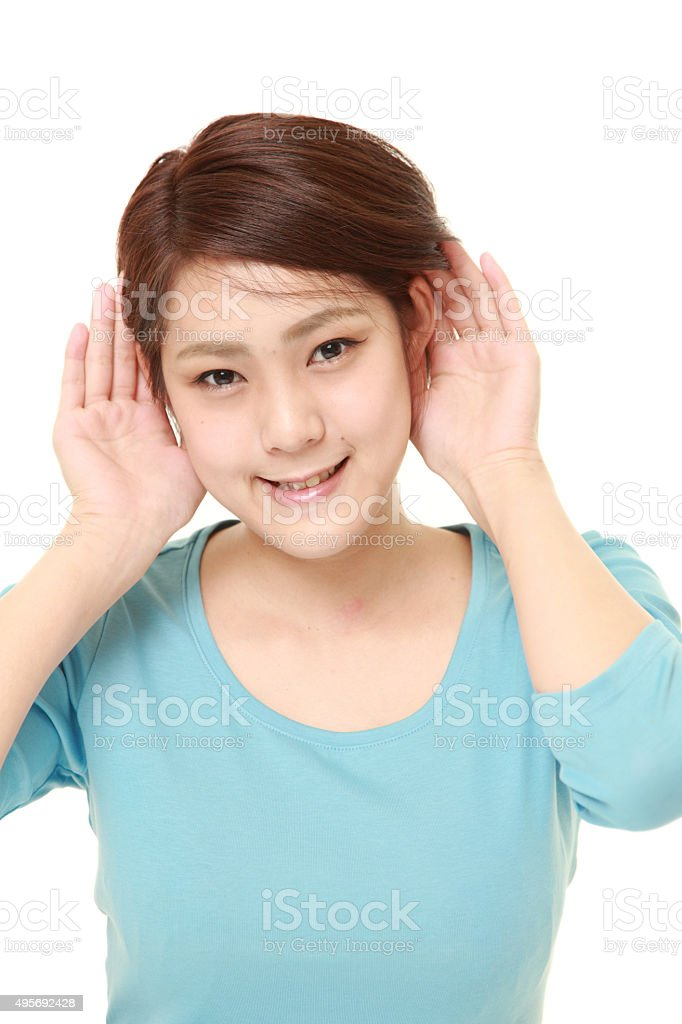 young woman with hand behind ear listening closely stock photo