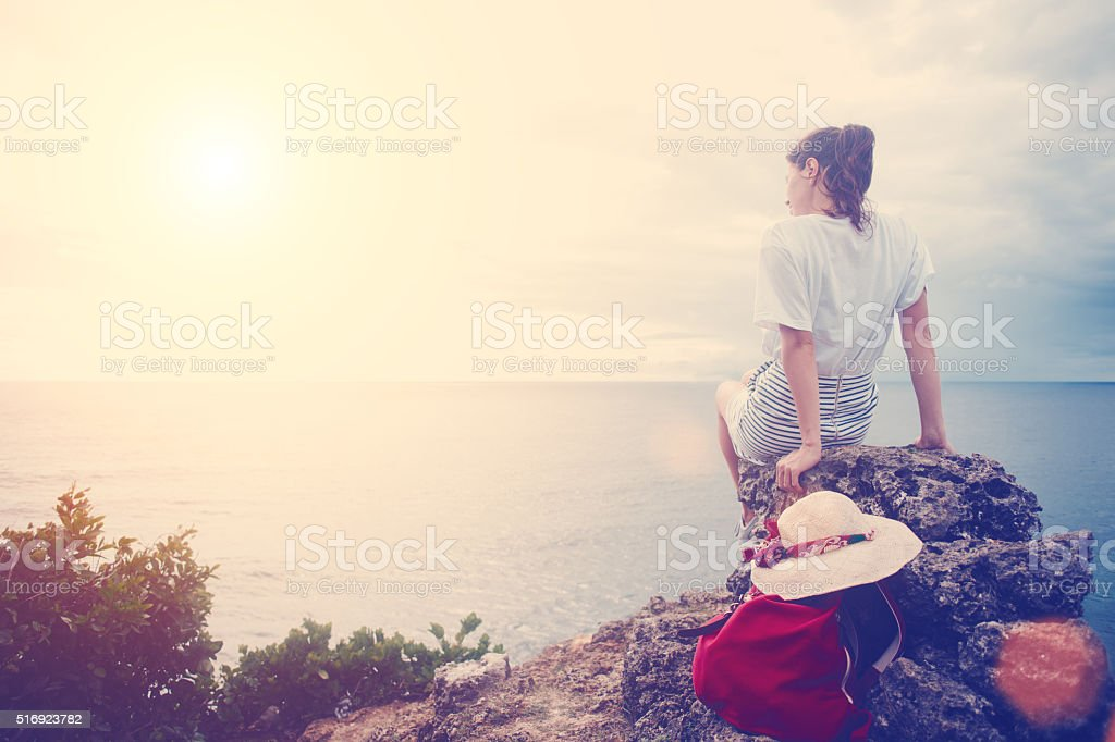 Young woman with hat and backpack sitting on a cliff stock photo