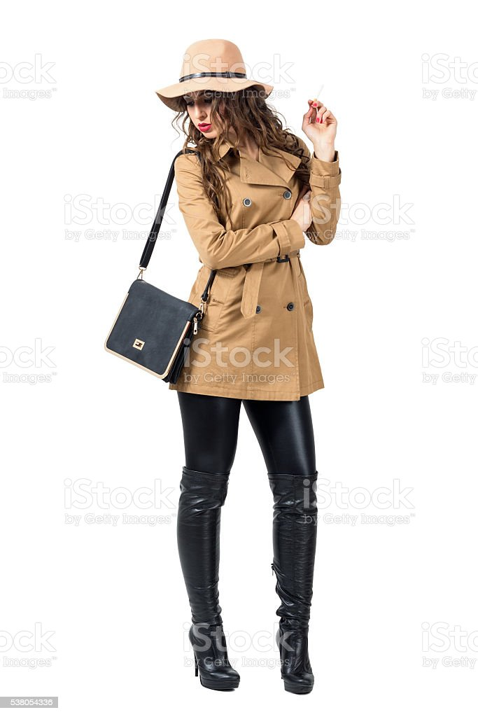 Young woman with hat and purse holding cigarette looking down. stock photo