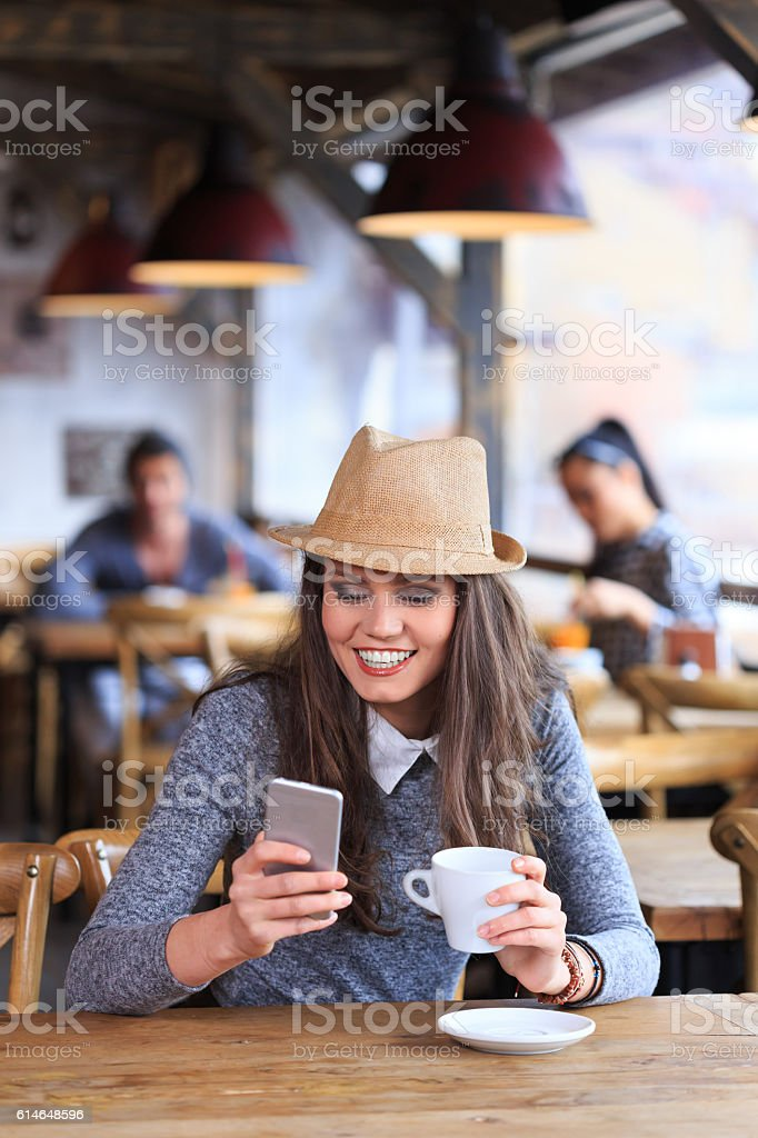 Young woman with hat having fun and drinking coffee stock photo