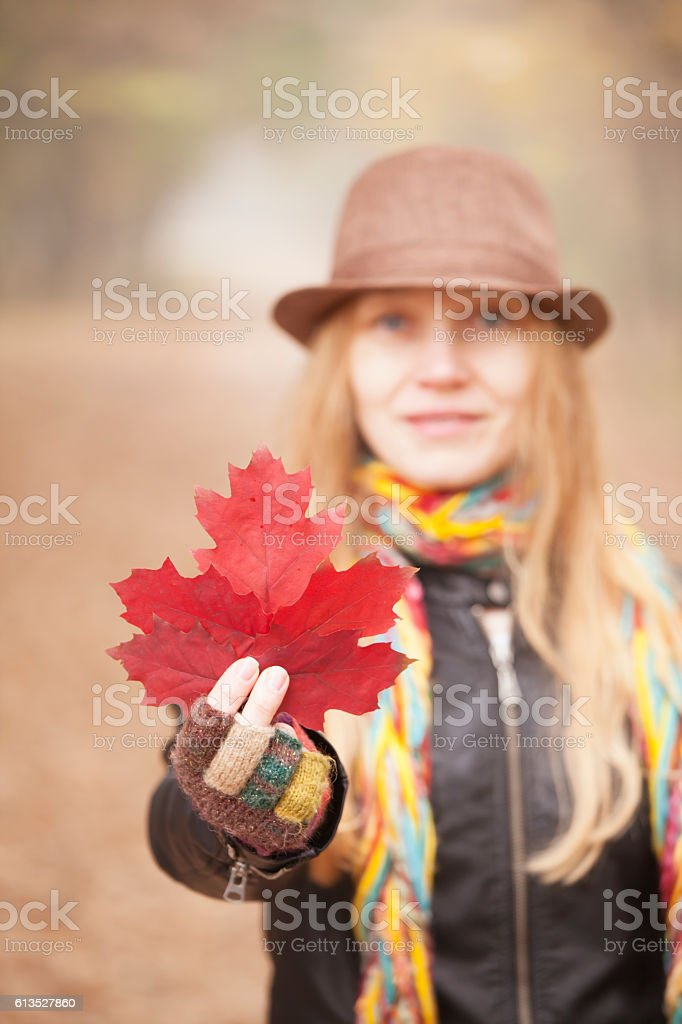 Young woman with hat holding red leaf stock photo
