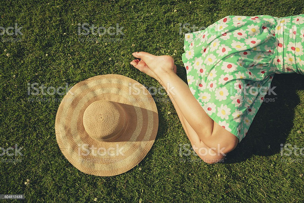 Young woman with hat sleeping in the park stock photo