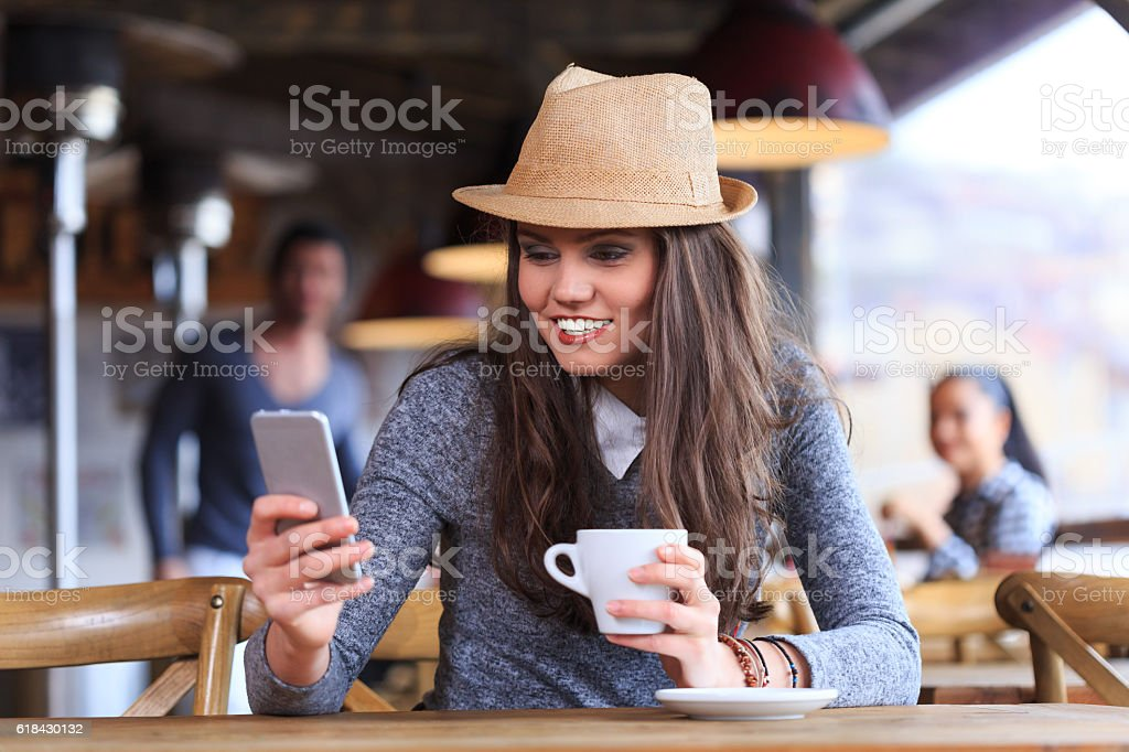 Young woman with hat using smart phone and drinking coffee stock photo