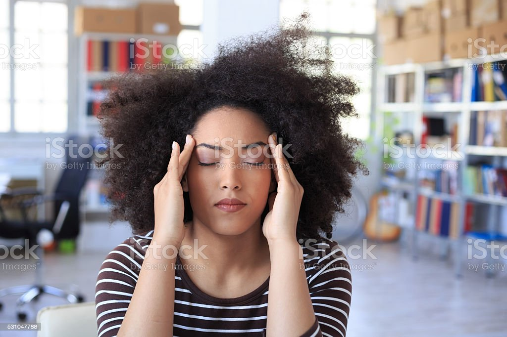 Young woman with headache at the office stock photo