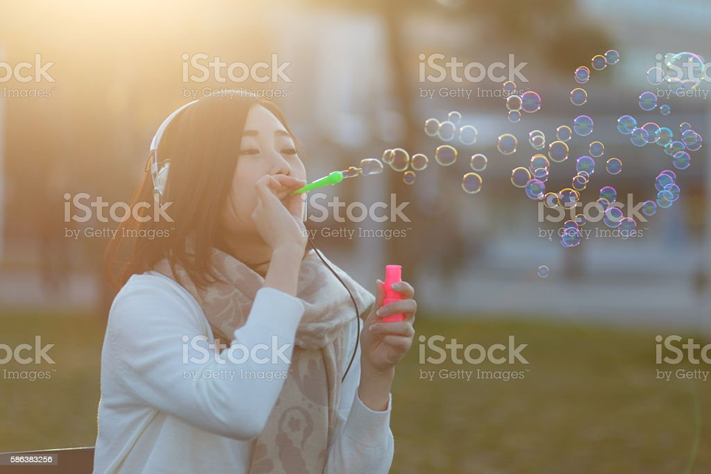 Young woman with headphones blowing bubbles in park stock photo