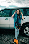 Young woman with headphones posing near car