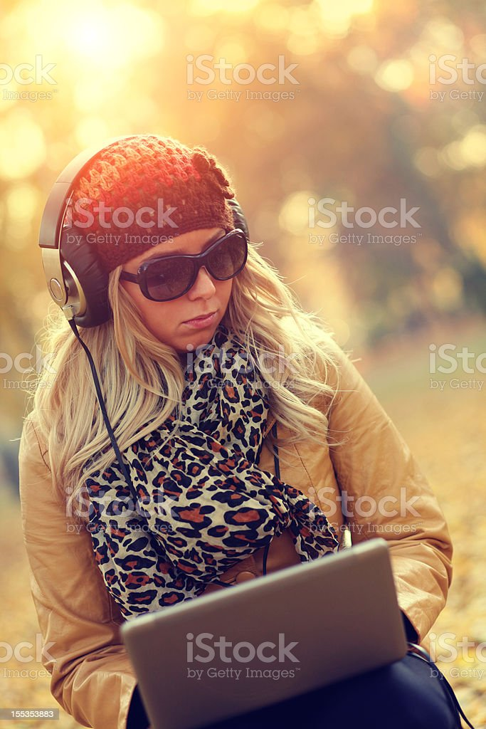 Young woman with headphones, sunglasses and hat royalty-free stock photo