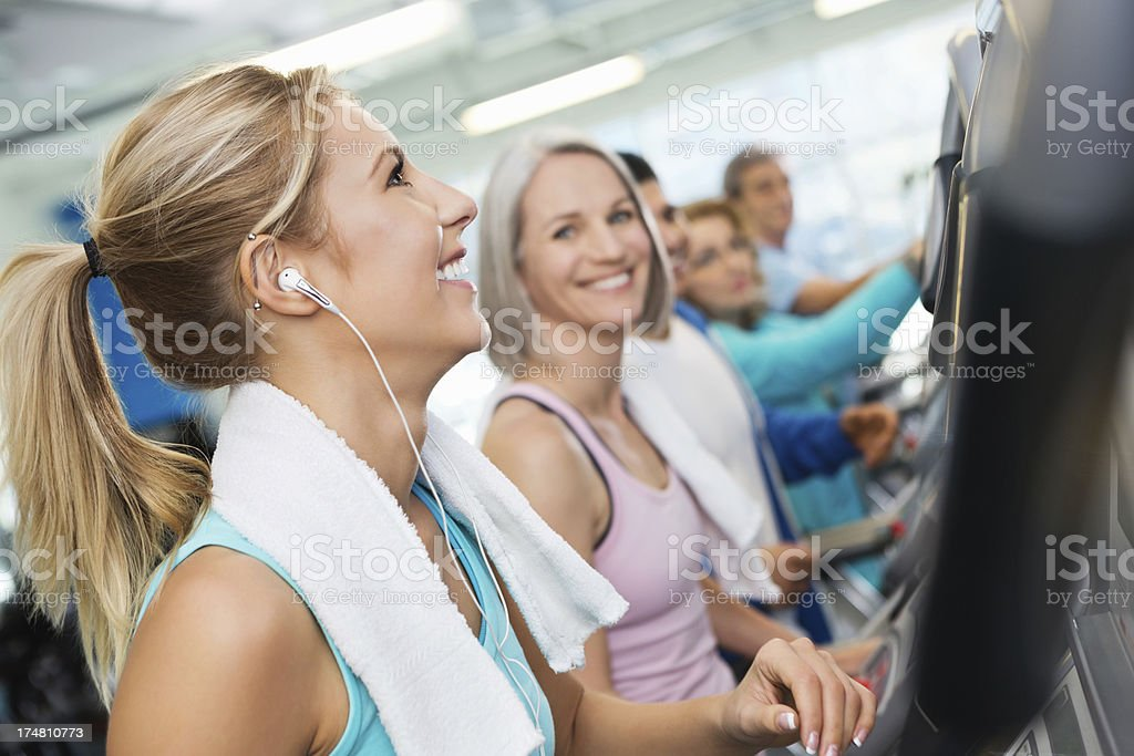 Young woman with headphones working out on treadmill in gym royalty-free stock photo