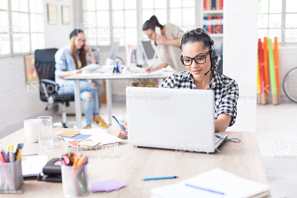 Young woman with headset using laptop at the office stock photo