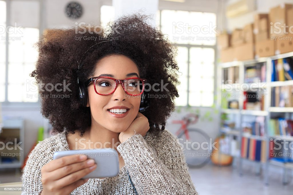 Young woman with headset using smart phone at workplace stock photo