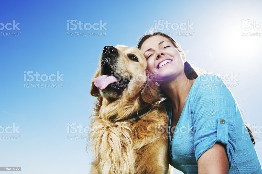 Young woman with her dog against the clear sky. stock photo