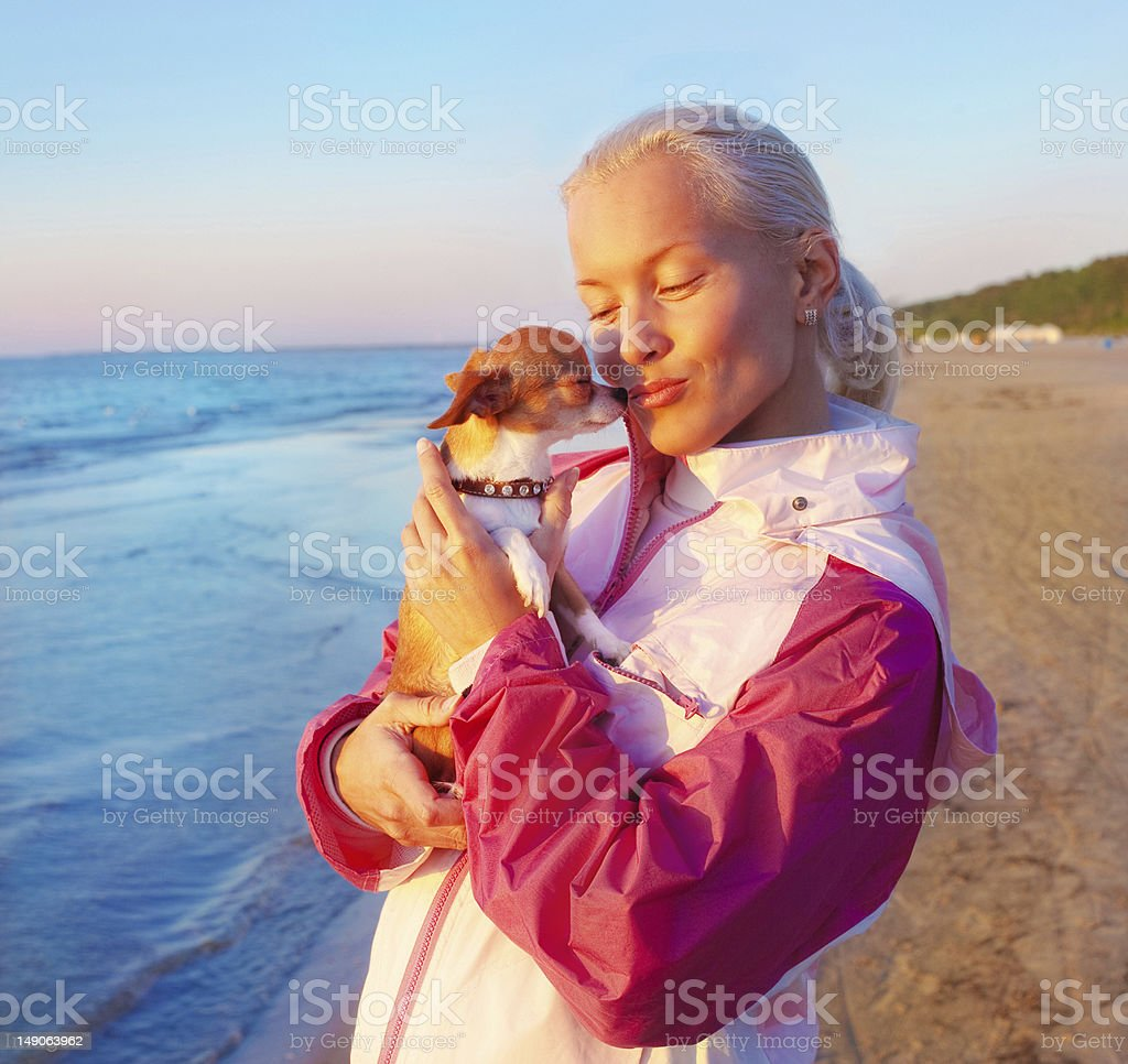 Young woman with her dog on a beach royalty-free stock photo