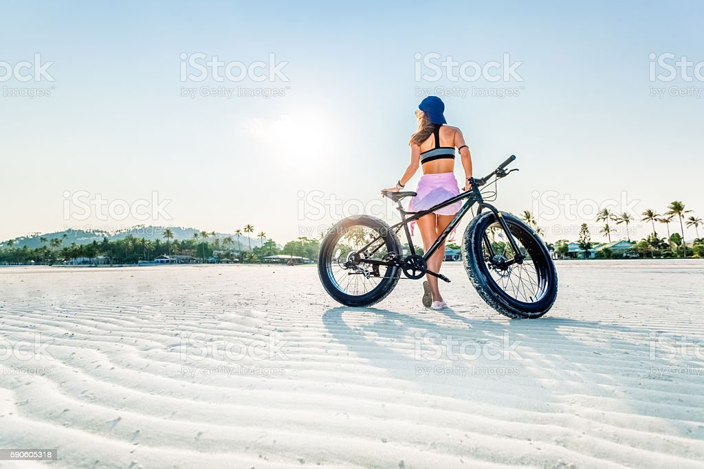 Young woman with her fat bike exercising on the beach stock photo