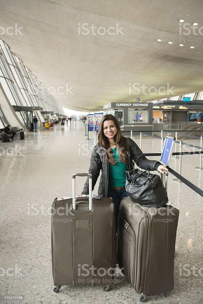 Young woman with her luggage at the airport terminal stock photo