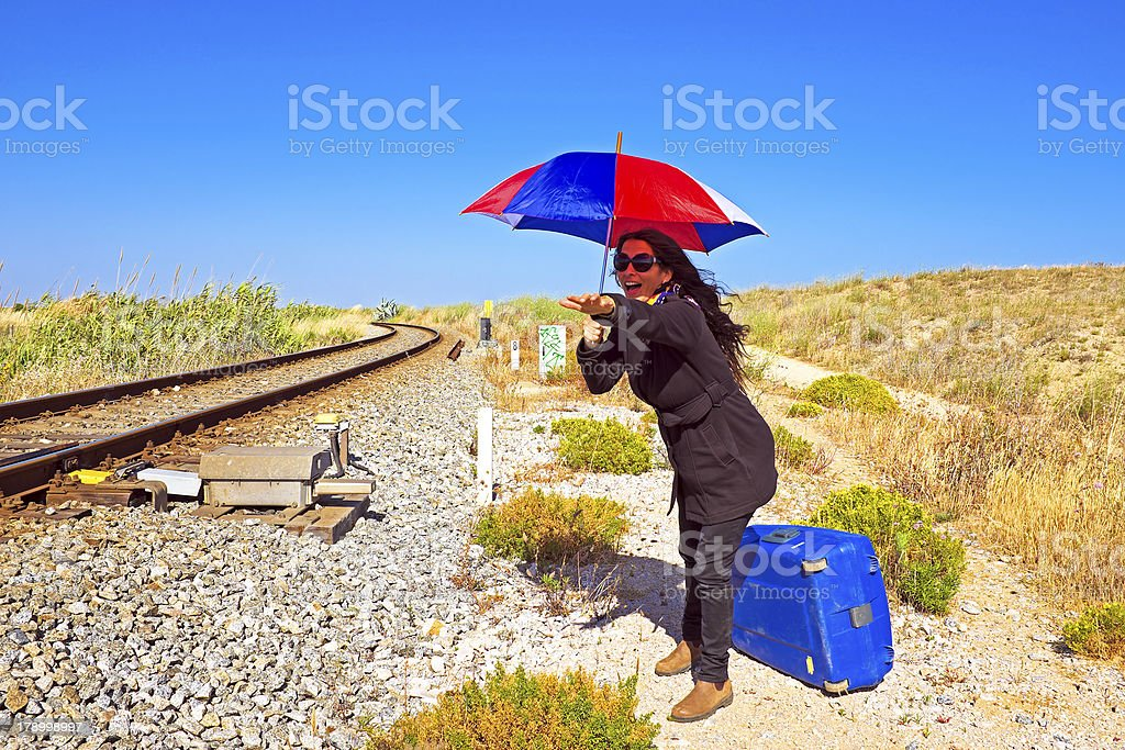 Young woman with her suitcase waiting at a railroad track royalty-free stock photo