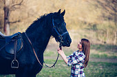 young woman with horse in spring sun nature