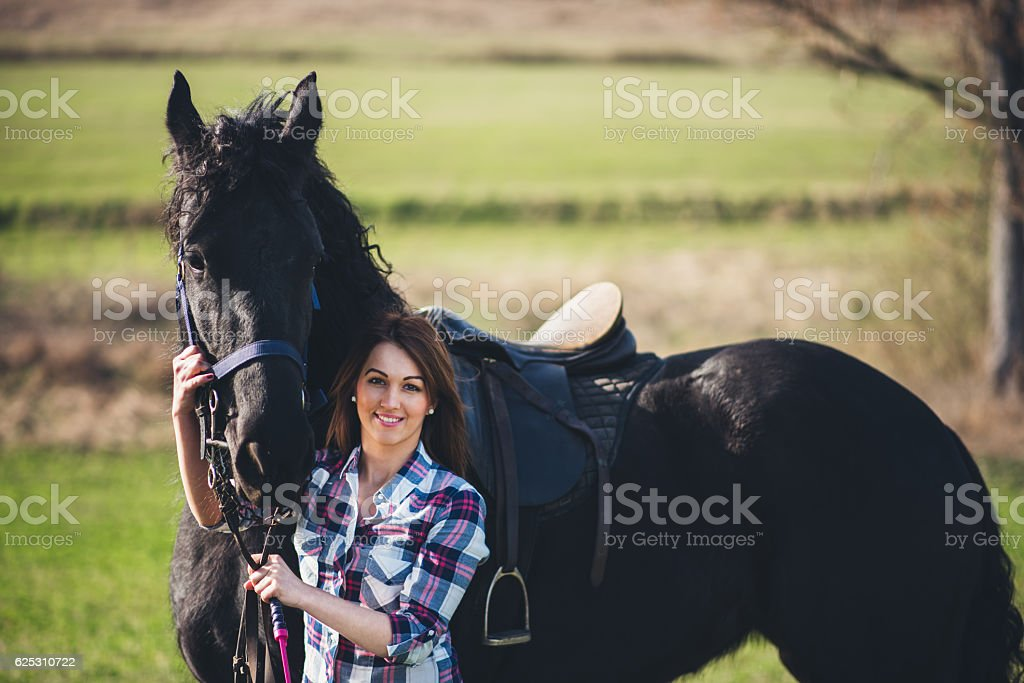 young woman with horse in spring sun nature stock photo