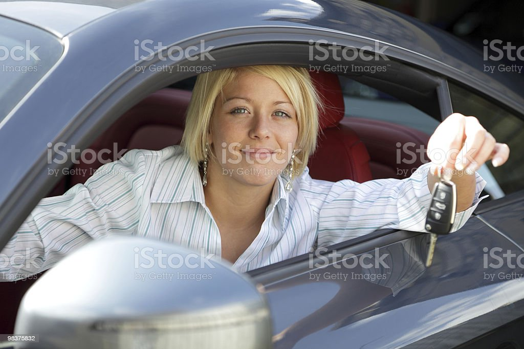 Young woman with keys of new, hire or rental car stock photo