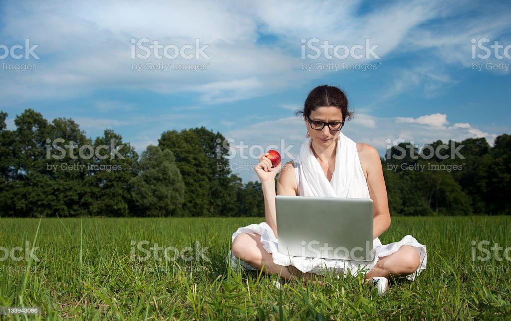 Young woman with laptop and peach royalty-free stock photo