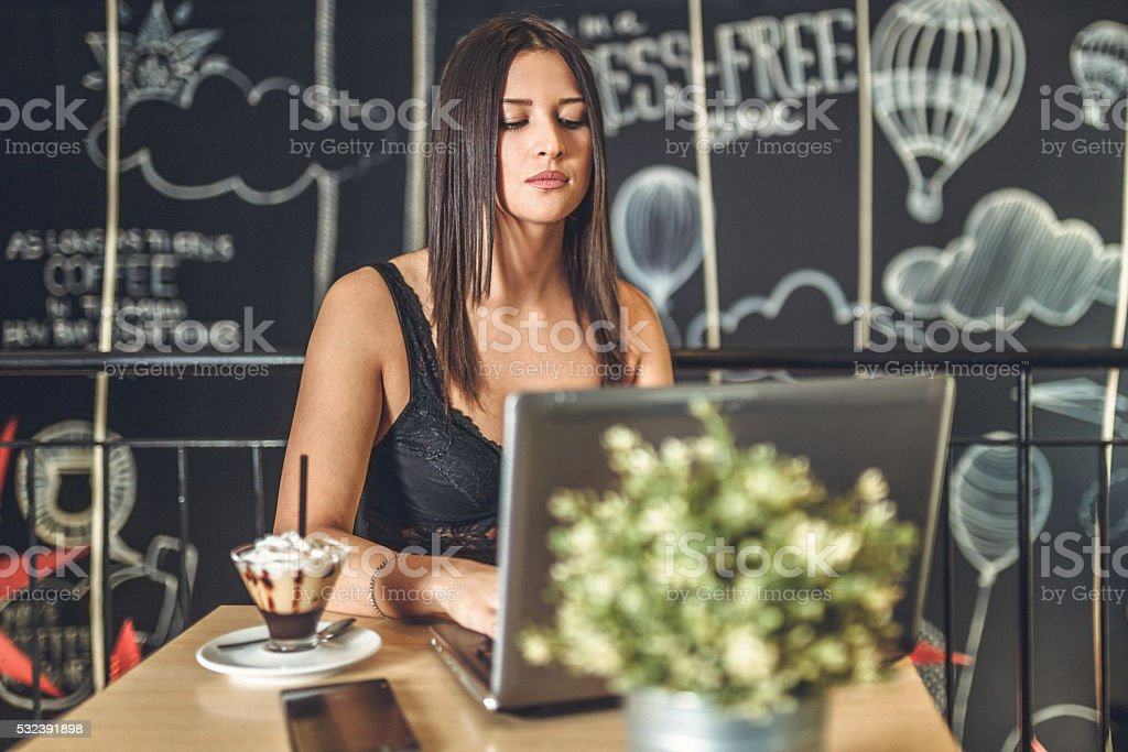 young woman with laptop at cafe stock photo