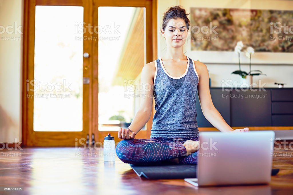 Young woman with laptop in lotus position at home stock photo