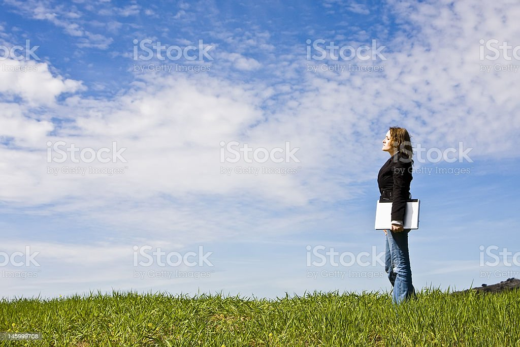 Young woman with laptop in meadow royalty-free stock photo