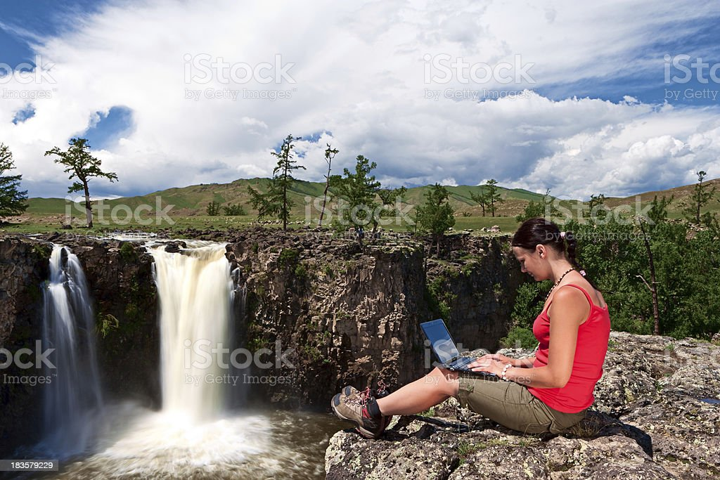 Young woman with laptop on rock stock photo