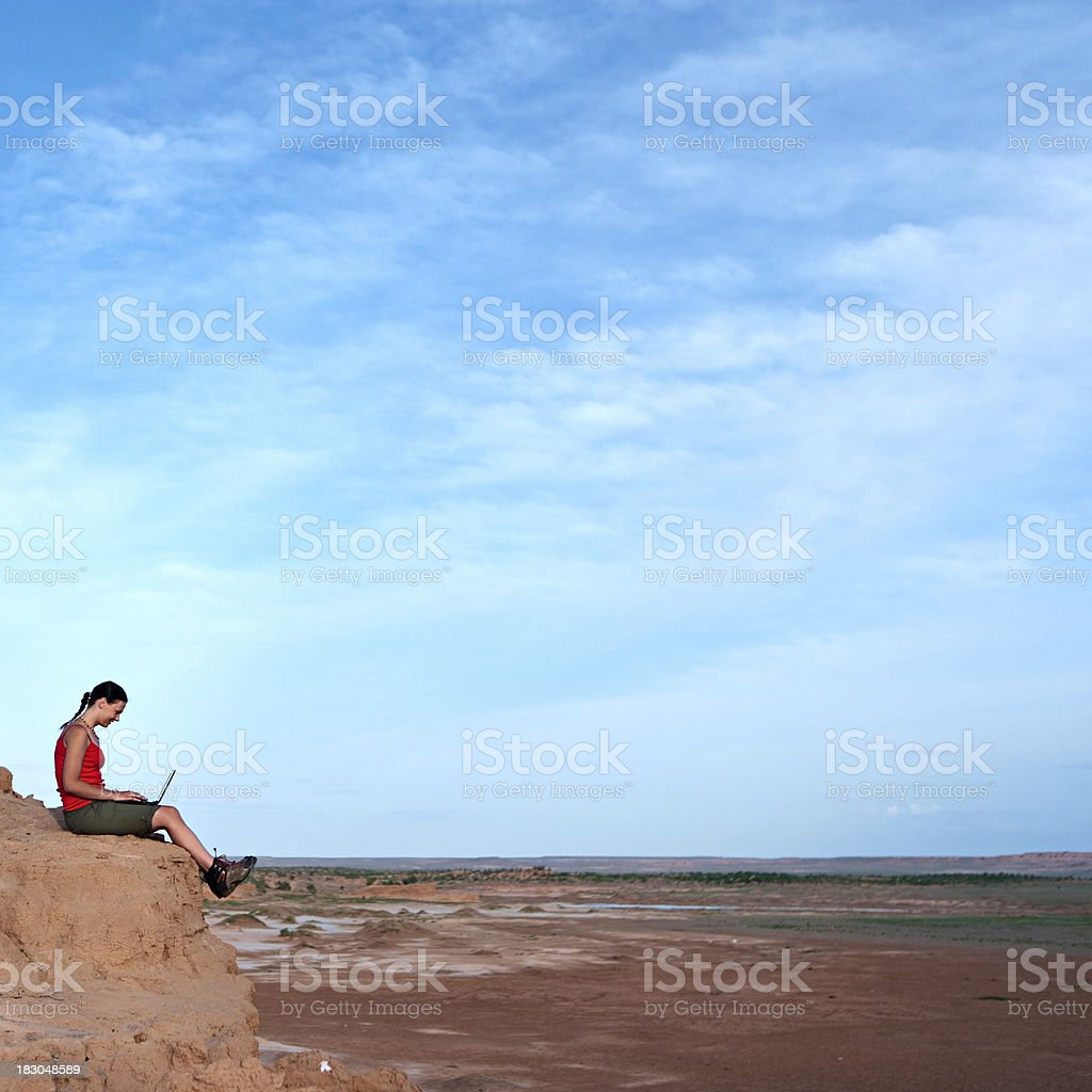 Young woman with laptop on the rock royalty-free stock photo