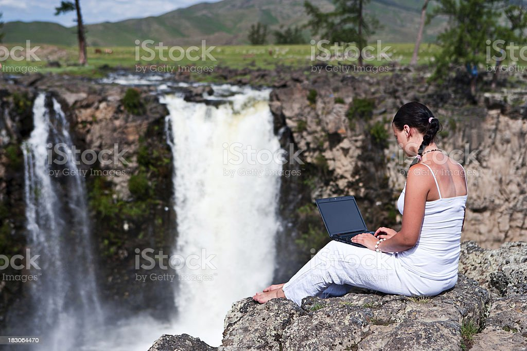 Young woman with laptop on the rock stock photo