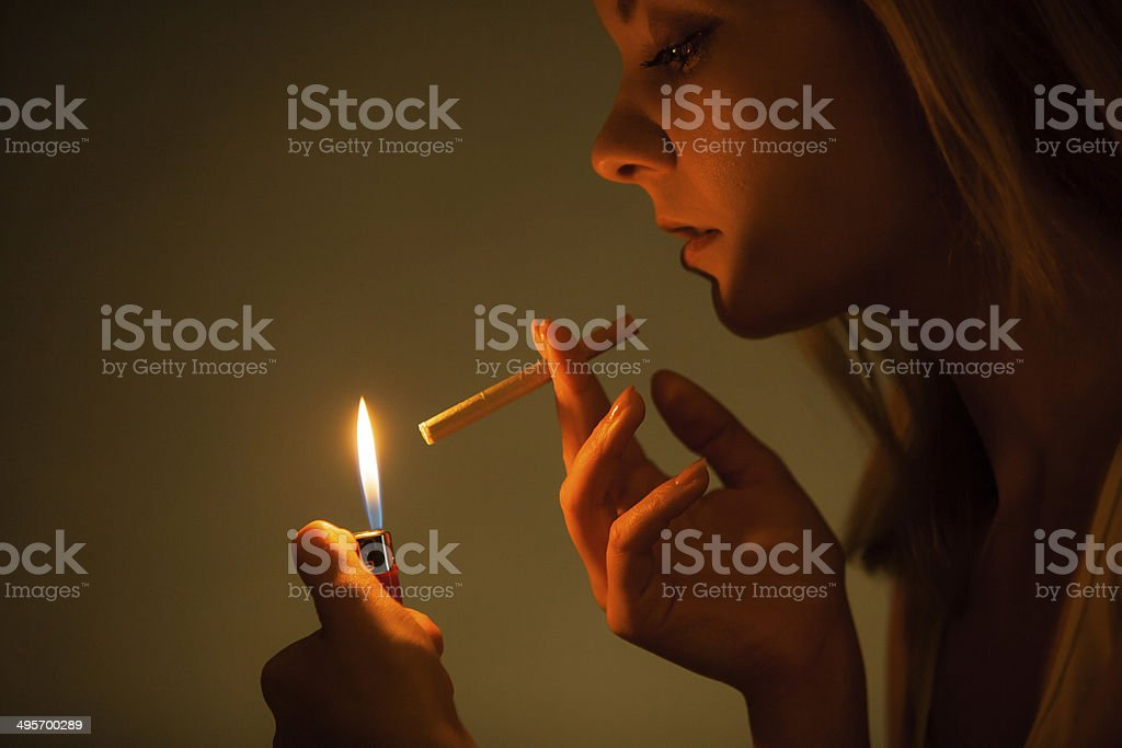 Young woman with lighter lighting up cigarette. Girl smoking. royalty-free stock photo
