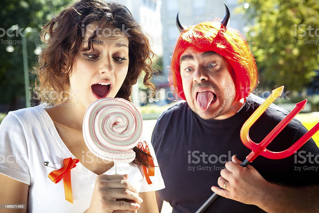 Young woman with lollipop and a devil in background stock photo