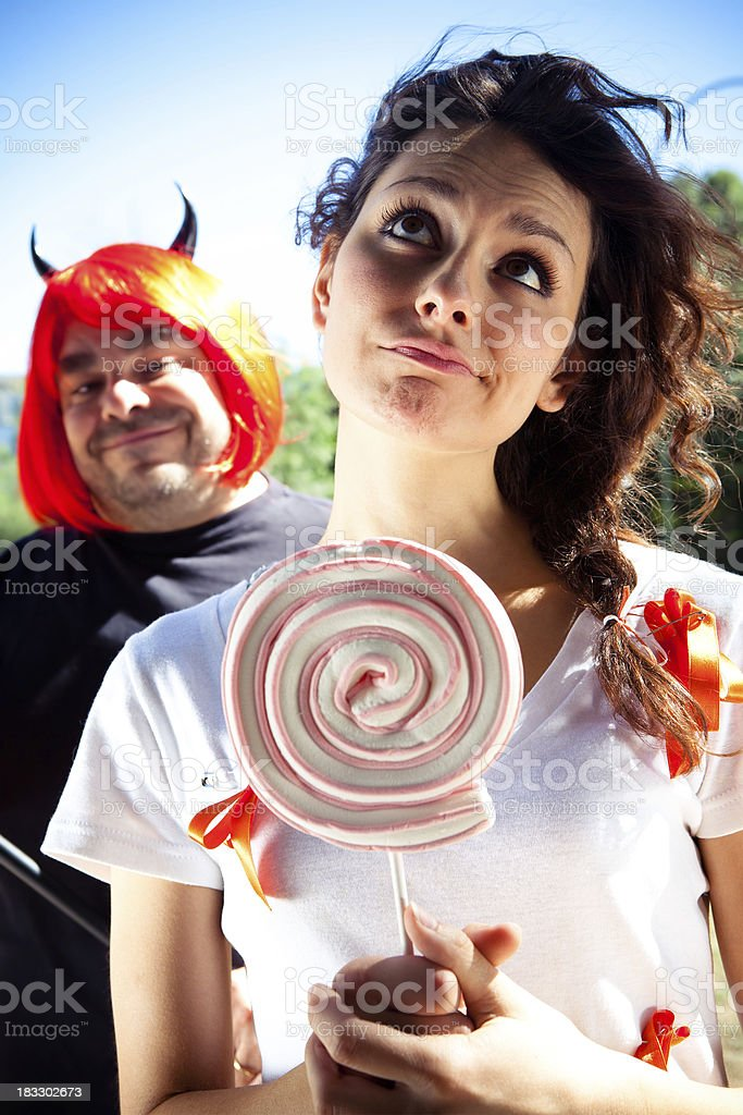 Young woman with lollipop and devil in background stock photo