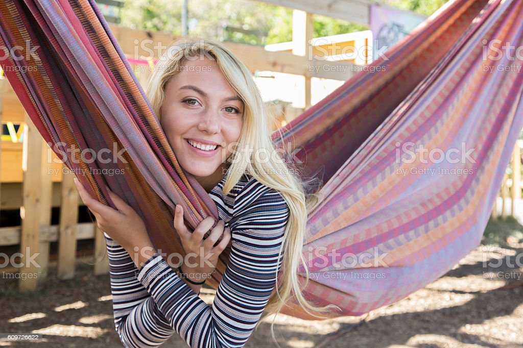 Young Woman with Long Blond Hair laying in a hammock stock photo
