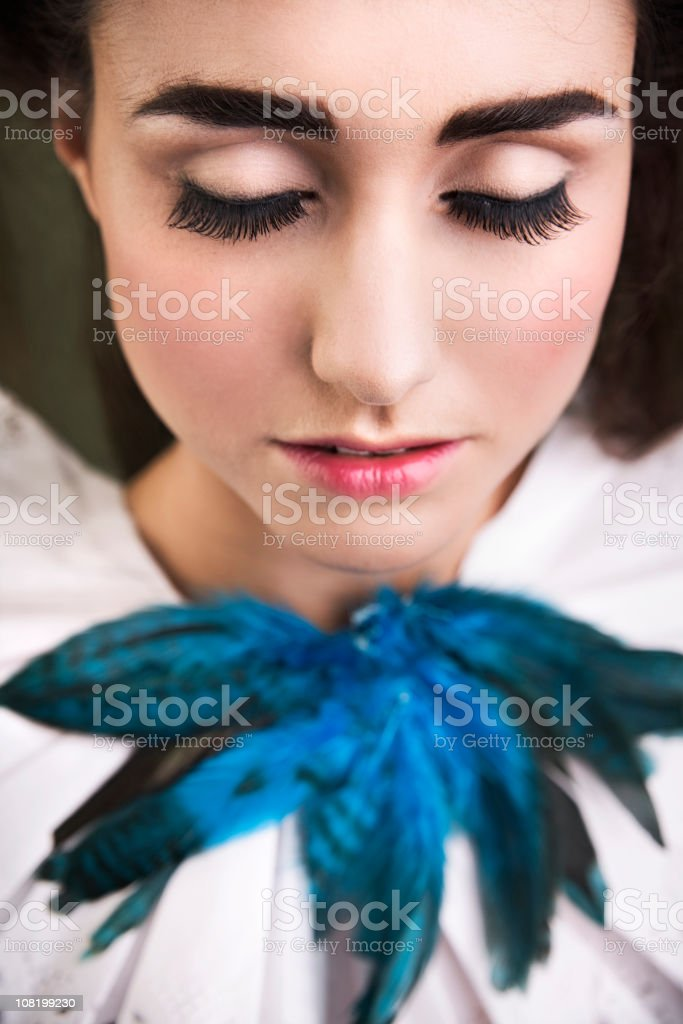 Young Woman with Long Eyelashes and Feathers on Sash Collar stock photo
