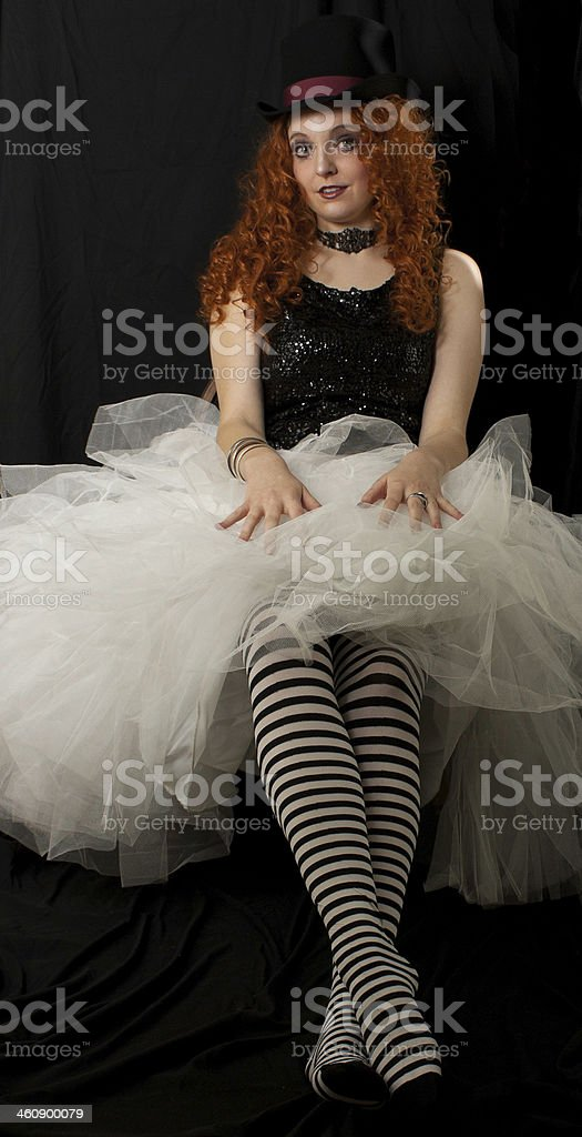 Young woman with long red hair in striped stockings royalty-free stock photo